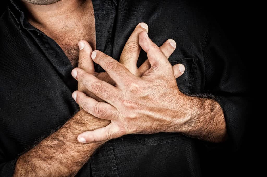 Close up of two hands grabbing a chest on a black background, us